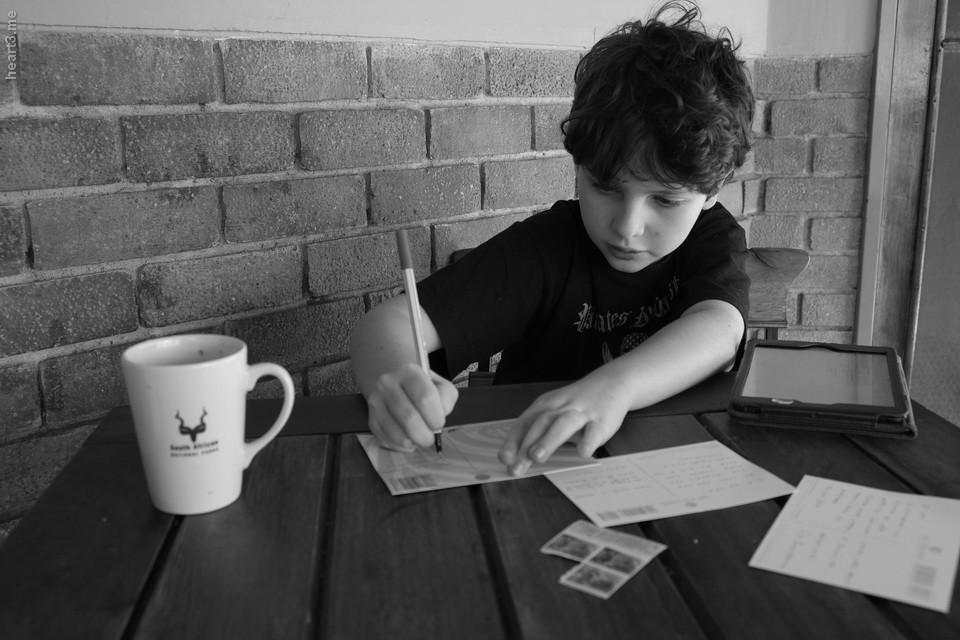 Dani escrevendo postais para mandar pro Brasil